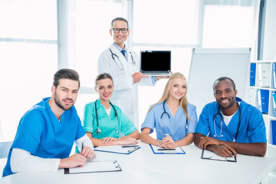Team of nurses and general practitioner with laptop having conference