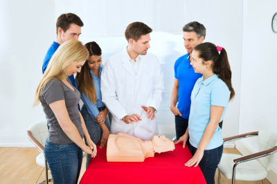 Mature Health Class Instructor Demonstrating Cpr Life Saving Techniques To Students