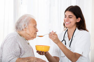 Happy Female Doctor Feeding Soup With Spoon To Senior Patient In Hospital