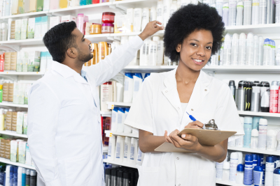 Portrait of female pharmacist writing on clipboard while colleague arranging products in shelves at pharmacy