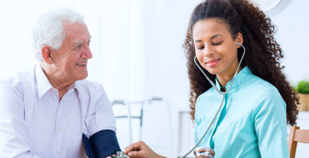 nurse checking blood pressure of senior man